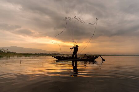 Silhouettes of the traditional stilt fishermen at sunset. Banque d'images