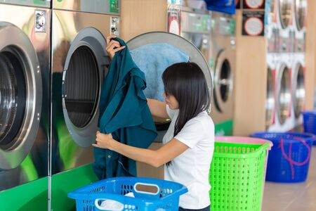 Side View Of A Young Woman Smelling Cleaned  Cloth Near Washing Machine