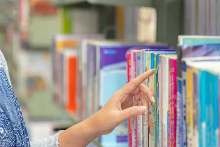 Asian women finding book and reading something at library. People adult female choosing a book on the bookshelf in a library. Education Concept Banque d'images