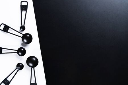 Black measuring spoons on black and white background.