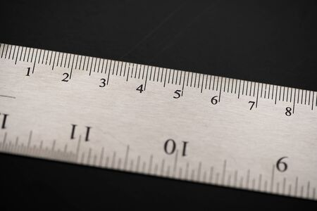 Metal ruler on a black leather isolated background with black numbers and scale. Show scale in black digit.