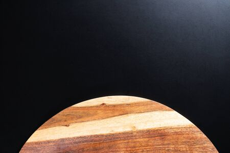 Wooden chopping board on black background.