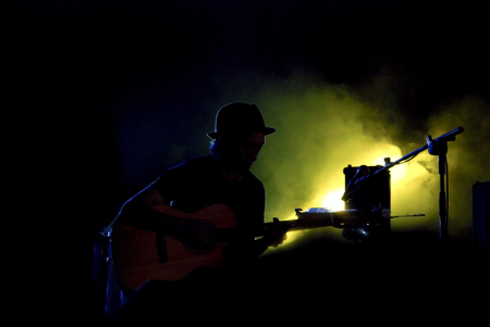 Silhouette of the playing Guitar under beams of yellow light on the stage Reklamní fotografie
