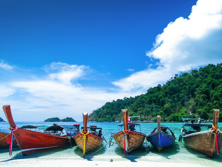 The passenger boat for tourism floating in the Andaman Thailand with mountain Blue sky and white cloud background