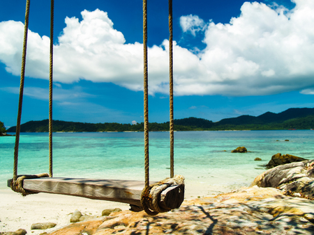 Wooden swing on the beach with blue sky and mountain background, Thailand
