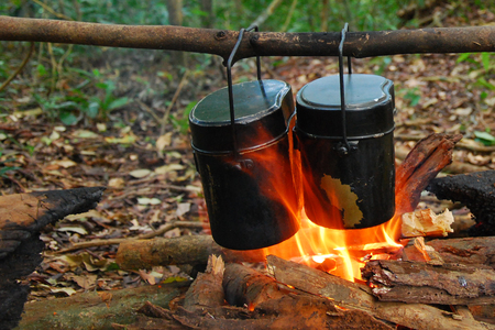 Food Is Cooked Over A Fire In An Old Vintage Retro Marching Pot Dixie. German Wehrmacht Infantry Soldiers Military Equipment Of World War II.