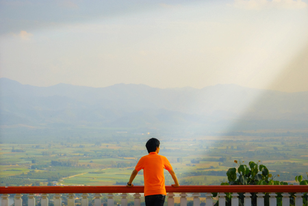 life concept. Outdoor shot beamlight of unrecognizable contemplating Asian tourist standing at wooden balcony sightseeing platform mountain view of resort city, wearing orange shirt