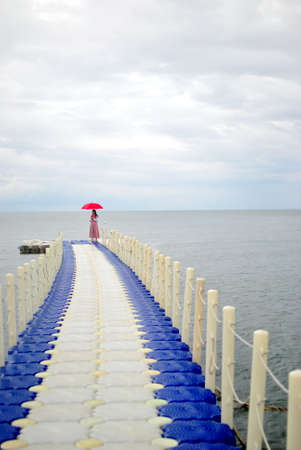 waterside: Girl and red umbrella on waterside