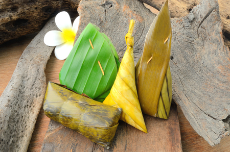 Thai dessert sticky rice wrapped in banana leaf on wood background.Thailand style food