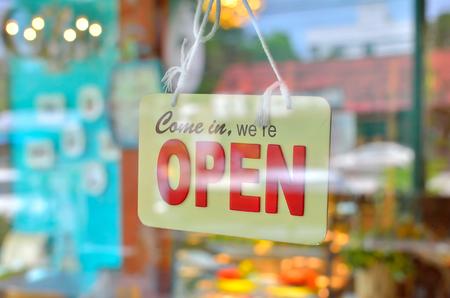 넓은 커피 숍에서 윈도우의 유리를 통해 오픈 기호