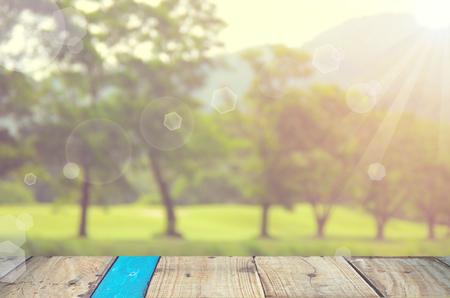 公園と自然をぼかし緑空の古い木製のテーブル背景ボケ味。