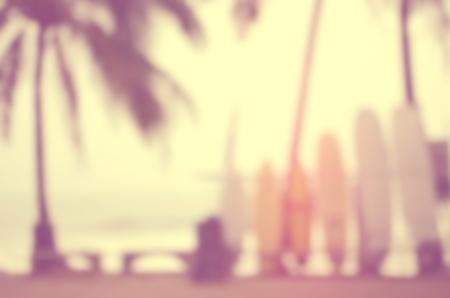 パーム ツリー抽象的な背景と熱帯のサンセット ビーチでサーフボードをぼかし。レトロなカラー スタイル。