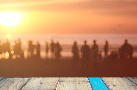 persone relax: Blur people relax on tropical sunset beach with old empty wood table background.