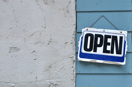 Old open sign hanging on wood background.