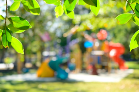 Blur playground in park with green leaf frame abstract background.
