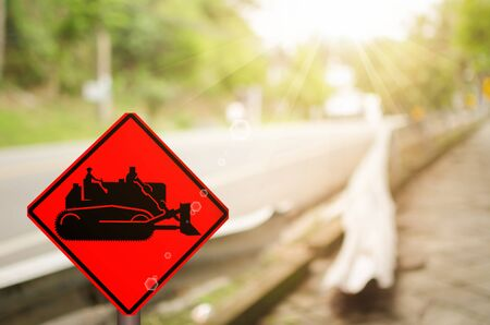 tractor warning sign: Traffic sign,construction tractor sign on blur traffic road abstract background.Retro color style. Stock Photo