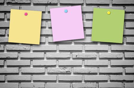 post it: Colorful post it note on black wall texture background. Stock Photo