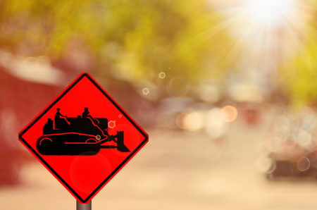 tractor warning: Traffic sign,construction tractor sign on blur traffic road abstract background.Retro color style. Stock Photo