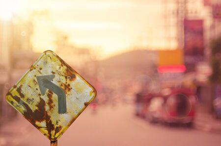 old sign: Traffic sign,old curve road sign on blur traffic road abstract background.Retro color style.