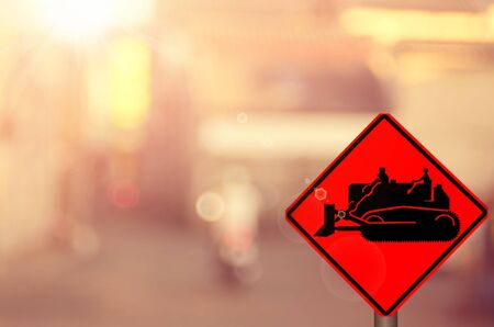 tractor sign: Construction tractor sign on blur traffic road abstract background.Retro color style. Stock Photo