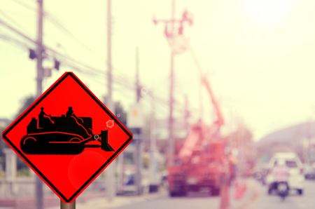 tractor warning: Construction tractor sign on blur worker repair electricity post at traffic road abstract background.Retro color style.