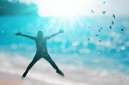 자유와 좋은 개념을 느낍니다. 실루엣의 공간을 복사 흐림 효과에 점프하는 행복 한 사람 조류와 열 대 해변 비행 추상적 인 배경입니다. 빈티지 톤 필