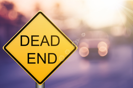 Dead end warning sign on blur traffic road with colorful bokeh light abstract background. Copy space of transportation and travel concept. Retro tone filter color style. Standard-Bild