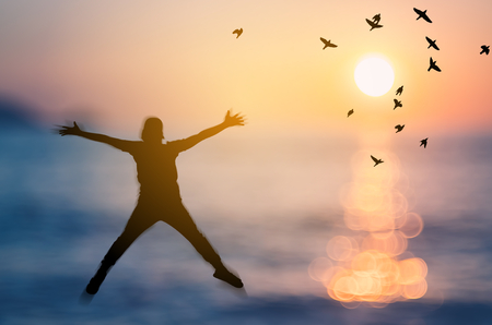 Libertà e sentirsi bene. Lo spazio della copia dell'uomo felice della siluetta che salta sulla spiaggia tropicale del tramonto della sfuocatura con gli uccelli vola il fondo astratto. Stile di colore del filtro tono vintage. Archivio Fotografico