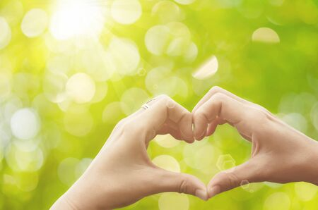 Female hands heart shape on nature green bokeh sun light flare and blur leaf abstract background. Copy space of happy love and freedom concept. Vintage tone color style. Stock Photo