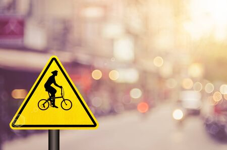 Bicycle warning sign on blur traffic road with colorful bokeh light abstract background. Transportation and travel concept. Retro tone color style. Stock Photo