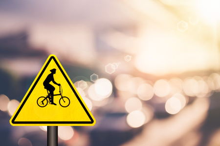 Bicycle warning sign on blur traffic road with colorful bokeh light abstract background. Copy space of transportation and travel concept. Retro tone filter color style.
