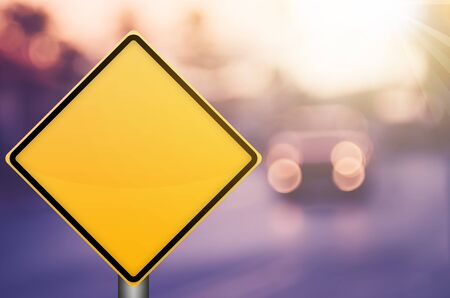 Empty yellow traffic sign on blur traffic road with colorful bokeh light abstract background. Copy space of transportation and travel concept. Retro tone filter color style. Stock Photo