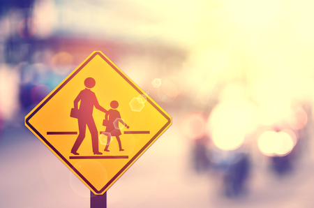 School zone warning sign on blur traffic road with colorful bokeh light abstract background. Copy space of transportation and travel concept. Vintage tone filter color style.