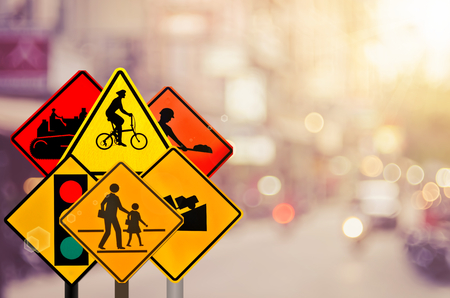 Set of traffic warning sign on blur traffic road with colorful bokeh light abstract background. Transportation and travel concept. Retro tone color style.
