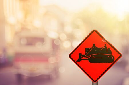 Traffic sign,construction tractor sign on blur traffic road abstract background.Retro color style. Stock Photo