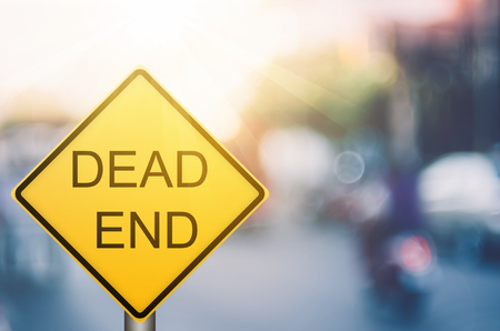 Dead end warning sign on blur traffic road with colorful bokeh light abstract background. Copy space of transportation and travel concept. Retro tone filter color style. Imagens