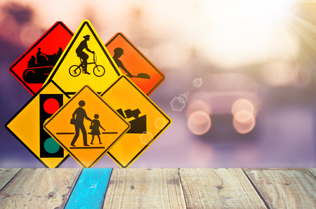 law school: Set of traffic warning sign on blur traffic road with colorful bokeh light and old empty wood table background.Copy space of transportation and travel concept. Product display presentation.Retro tone