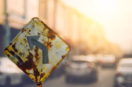 Old curve road warning sign on blur traffic road with colorful bokeh light abstract background. Copy space of transportation and travel concept. Retro tone filter color style. Stock Photo