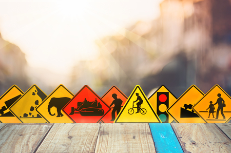 Set of traffic warning sign on blur traffic road with colorful bokeh light and old empty wood table background.Copy space of transportation and travel concept. Product display presentation.Retro tone