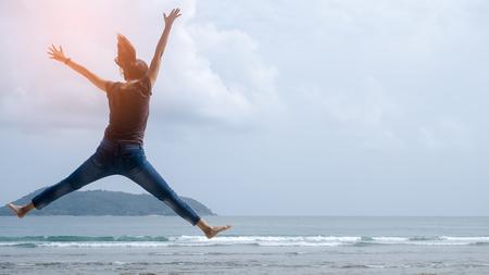 기분 좋은 자유 개념. 해변에서 점프하는 행복 한 여자의 공간을 복사합니다. 빈티지 톤 필터 색상 스타일입니다.