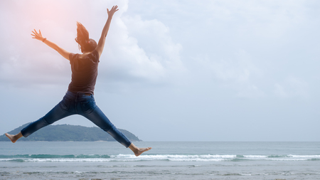Feel good and freedom concept. Copy space of happy woman jumping on beach. Vintage tone filter color style. Standard-Bild