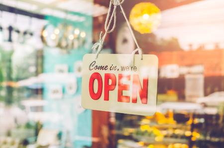 Abra la muestra ancha a través del vidrio de la puerta en café. Servicio de negocios y concepto de comida. Estilo del color del filtro del tono de la vendimia.