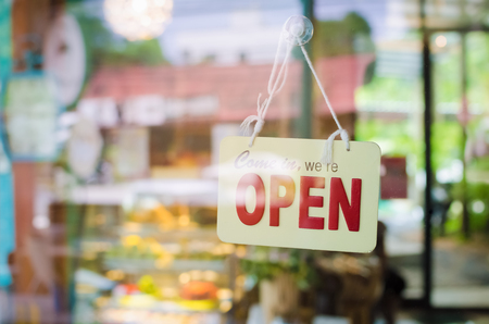 カフェのドアのガラスを通して広いオープン サイン。ビジネスとサービスの概念。