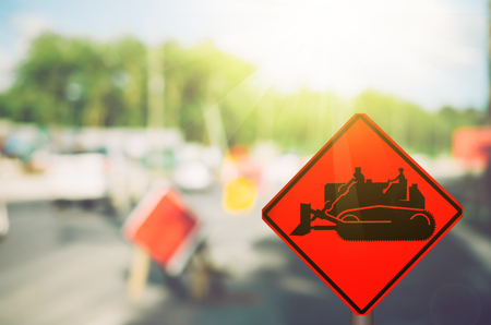 Construction tractor warning sign on blur damage road abstract background. Copy space of transportation and travel concept. Vintage tone filter color style.