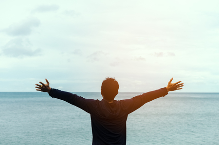 Feel good and freedom concept. Copy space of happy man raise hands on beach background. Vintage tone filter color style.