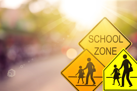Set of School zone warning sign on blur traffic road with colorful bokeh light abstract background. Copy space of transportation and travel concept. Vintage tone filter color style.