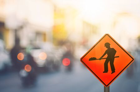 Construction warning sign on blur traffic road with colorful bokeh light abstract background. Copy space of transportation and travel concept. Retro tone filter color style.