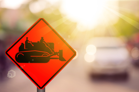 Construction tractor warning sign on blur traffic road with colorful bokeh light abstract background. Copy space of transportation and travel concept. Retro tone filter color style. Stock Photo