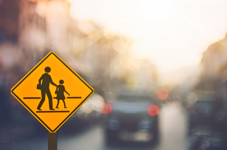 School zone warning sign on blur traffic road with colorful bokeh light abstract background. Copy space of transportation and travel concept. Vintage tone color style.