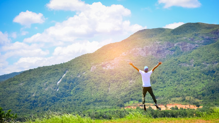 achiever: Feel good and freedom concept. Copy space of happy man jumping on top of mountain. Vintage tone filter color style.